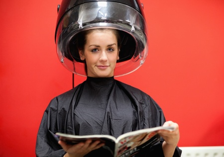 Young woman under a hairdressing machine while reading a magazine photo