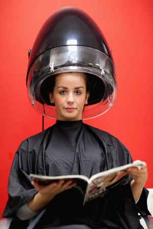 Portrait of a cute woman under a hairdressing machine while reading a magazine photo