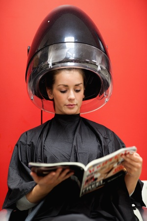 Portrait of a student under a hairdressing machine while reading a magazine photo