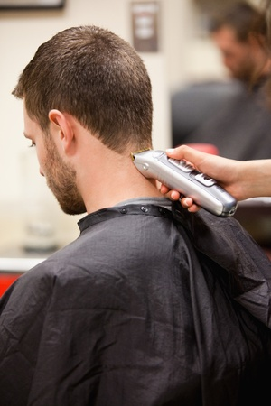 shorten: Portrait of man having a haircut with a hair clippers Stock Photo