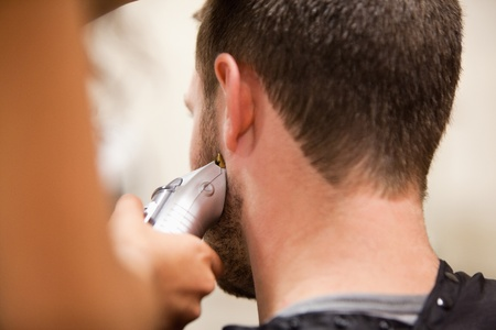Young man having a haircut with a hair clippers photo