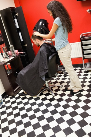 Portrait of a male student having a haircut with a hair clippers photo