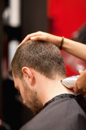 black barber: Portrait of a male young student having a haircut with a hair clippers Stock Photo