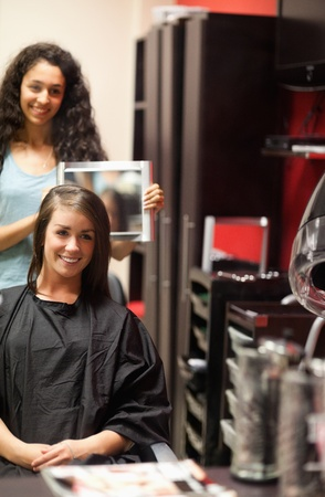 Portrait of a hairdresser showing to her customer her new haircut with a mirror photo