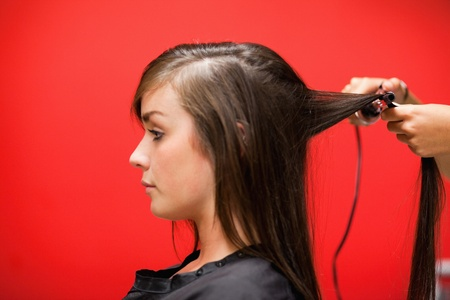 Woman having her hair straightened against a red background photo