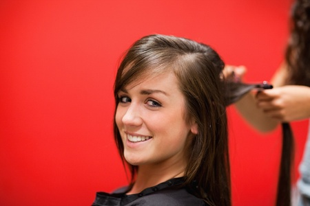 Young woman having her hair straightened while looking at the camera photo