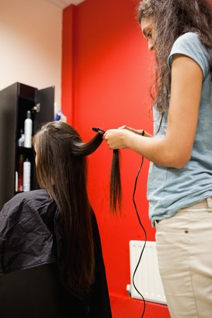 Portrait of a woman straightening hair with a hair straightener photo