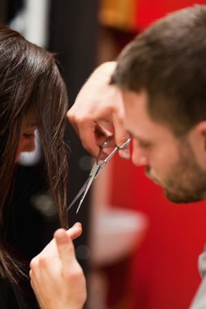 Portrait of a male hairdresser cutting hair with scissors photo
