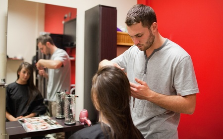Male hairdresser cutting hair with scissors photo