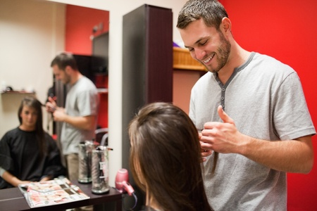 dresser: Smiling male hairdresser cutting hair with scissors