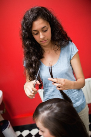 Portrait of a young female hairdresser cutting hair with scissors photo