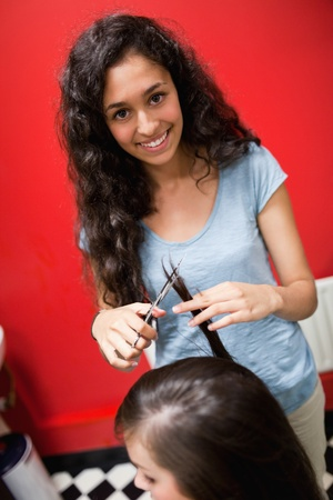 style advice: Portrait of a smiling female hairdresser cutting hair with scissors