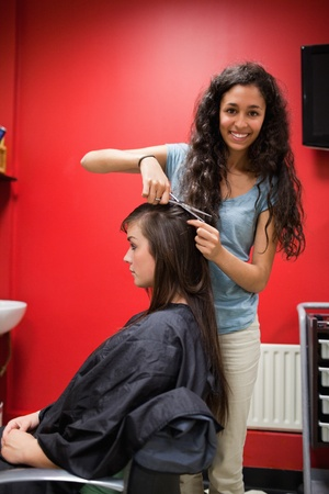 Portrait of a happy female hairdresser cutting hair with scissors photo