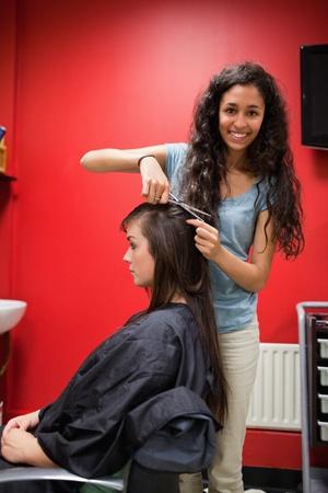 saloon: Retrato de una mujer feliz peluquero corte de pelo con tijeras Foto de archivo