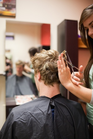 Portrait of a blond-haired man having a haircut with scissors photo