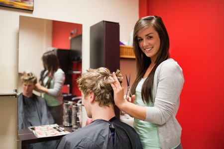 coiffeur: Blond-haired young man having a haircut with scissors Stock Photo