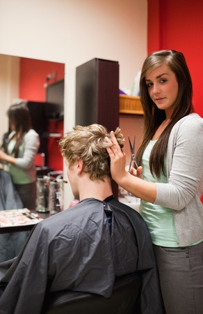 Portrait of a young woman cutting a man's hair with scissors Stock Photo - 11182994