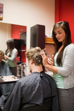 Portrait of a focused woman cutting a mans hair with scissors photo