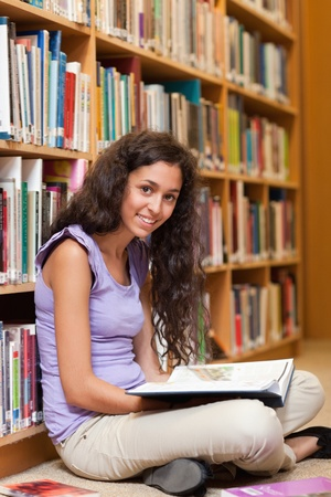 Portrait of a female student with a book in a library photo
