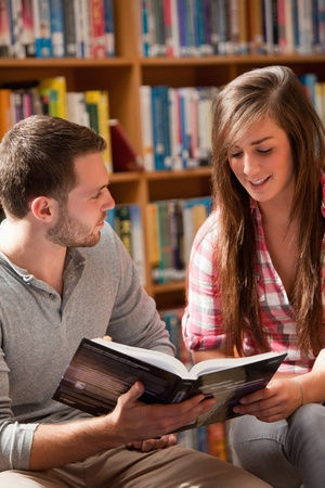 Portrait of students reading a book in a library photo