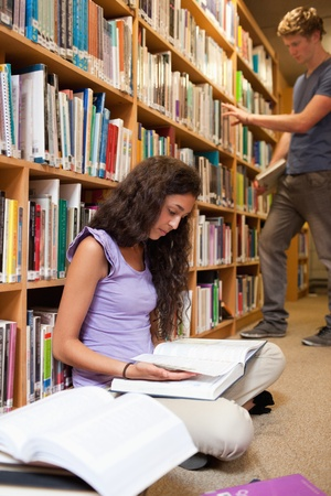 Portrait of a student reading a book while her classmate is choosing a book in a library photo