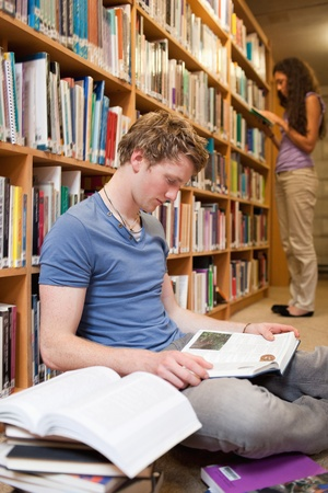 Portrait of a male student reading books while his classmate is reading in a library photo