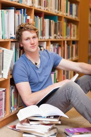 Portrait of a male student with a book in a library photo