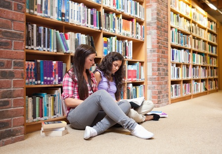 Female students with a book in a library photo