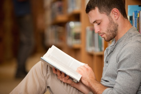 Serious male student reading a book in a library photo