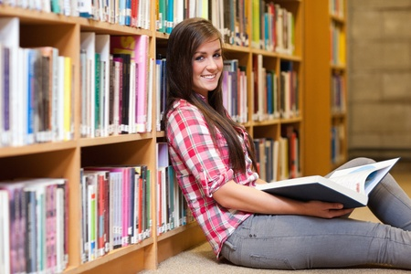Smiling young female student holding a book in a library photo