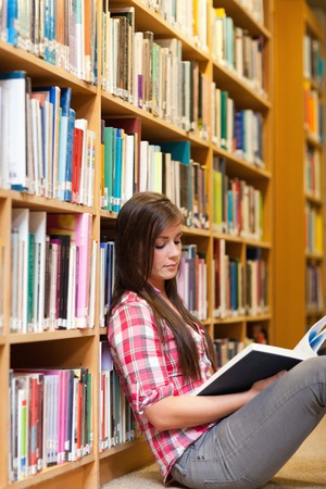 library student: Portrait of a young female student reading a book in a library