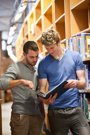 Portrait of male students looking at a book in a library photo