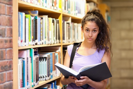 Serious female student holding a book in a library photo