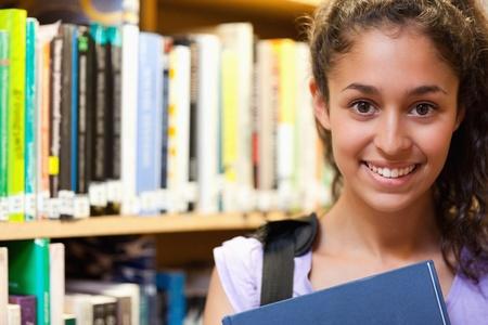 Gl�cklich Sch�lerin h�lt ein Buch in einer Bibliothek