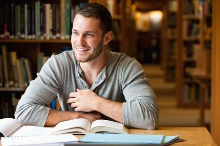biblioteca: Estudiante sonriente masculino para trabajar en una biblioteca