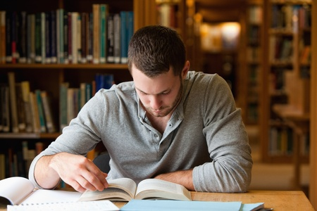 study: Male student researching with a book in a library Stock Photo