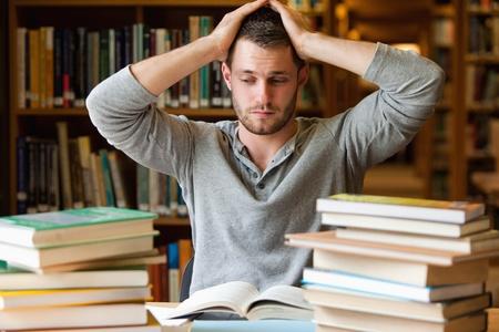 M�de Sch�ler mit zu viel, um in einer Bibliothek zu tun Stockfoto