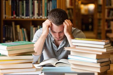 hombre estudiando: Estudiante cansado tener mucho que leer en una biblioteca Foto de archivo