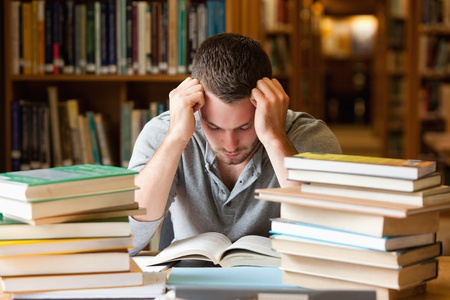 difficulties: Tired student having a lot to read in a library