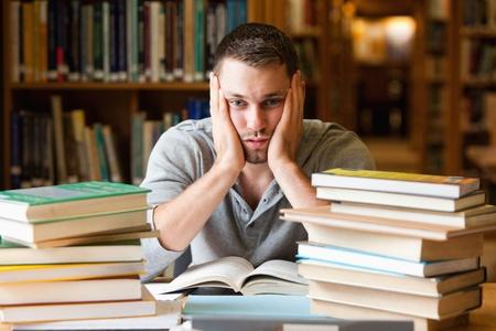 Depressieve student met een veel te lezen kijken naar de camera Stockfoto