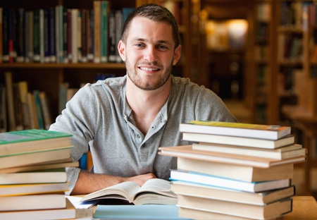 Smiling student surrounded by books in a library photo