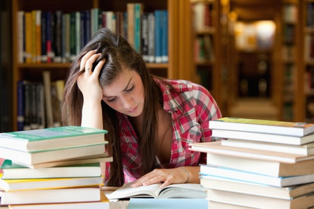 examination stress: Focused student surrounded by books in a library