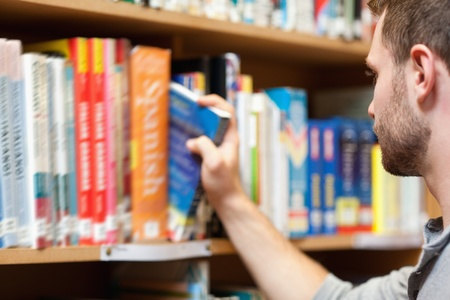 Handsome male student picking a book in a library photo