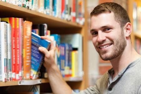 handsome student: Smiling male student picking a book in a library Stock Photo