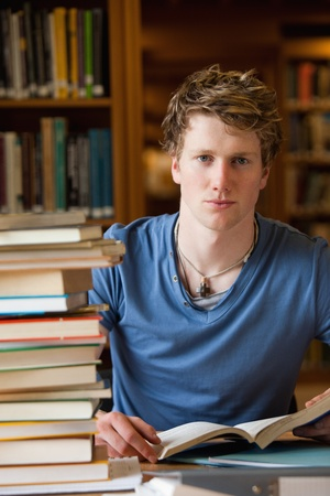 Portrait of a male student posing with books in a library photo