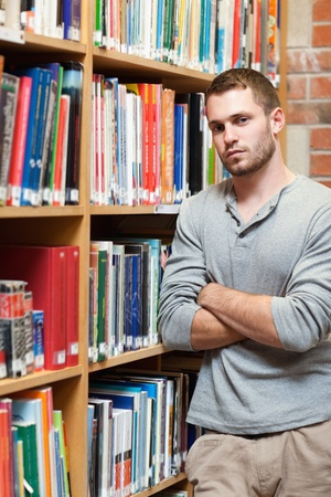 Portrait of a male student leaning on a shelf in a library Stock Photo - 11181829
