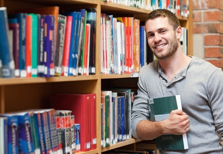 Smiling male student holding a book in a library Stock Photo - 11182013