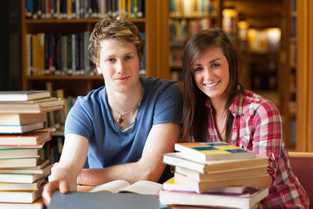 Smiling students surrounded by books in a library photo