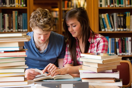Serious students looking at a book in a library Stock Photo - 11181432