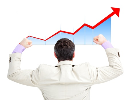 Successful businessman with the fists up looking at a growing curve photo